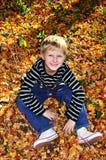 Glücklicher Junge im sonnigen Herbstwald Stockbild