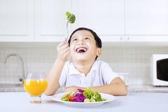 Junge, der am grünen Brokkoli in der Küche lacht Stockfotos