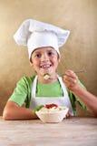 Glücklicher Junge mit Chefhut Teigwaren essend Stockfotos