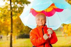 Glücklicher Junge mit dem blauen Regenschirm, der unter Regen steht Stockfotografie