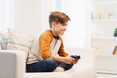 Glücklicher Junge mit dem Steuerknüppel, der zu Hause Videospiel spielt stockbild