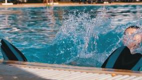 Gl?cklicher Junge mit Flippern schwimmt in einem Pool mit blauem Wasser Langsame Bewegung