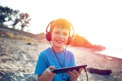 Glücklicher Junge mit Kopfhörern und Tablette im Sonnenuntergang stockbild