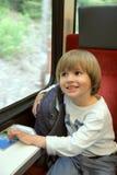 Glücklicher Junge mit Rucksack auf Zug Stockfotos
