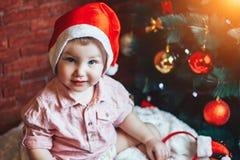 Glücklicher Junge mit Weihnachtsdekorationen nähern sich Weihnachtsbaum Betrachten der Kamera stockfoto