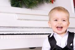 Glücklicher Junge nahe weißem Klavier Stockfotos