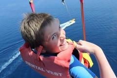 Glücklicher Junge Parasailing hoch über dem Meer Stockbild