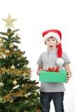 Glücklicher Junge in Sankt-Hut überrascht durch Weihnachtsgeschenk Stockfotografie