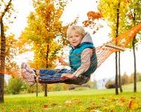 Glücklicher Junge sitzt auf Netz der Hängematte im Park Stockbild