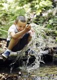 Glücklicher Junge spielt mit Wasser stockfotografie