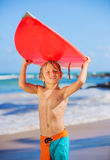 Glücklicher Junge am Strand mit Surfbrett Stockfotos