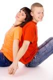 Glücklicher Junge und ein Mädchen, das mit ihr, zurück gedrückt sitzt Lizenzfreies Stockfoto