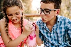 Glücklicher Junge und Mädchen in der Liebe, die Spaß ein Smoothie outdoo trinkend hat lizenzfreie stockfotografie