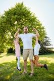 Glücklicher Junge und Mädchen, die an den Muskeln des Vaters hängt Lizenzfreies Stockbild