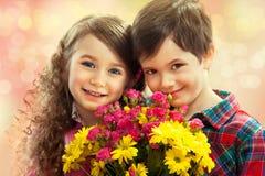 Glücklicher Junge und Mädchen mit Blumenstrauß von Blumen. stockfotografie