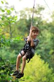 Glücklicher Junge verabschiedete erfolgreich den Hindernislauf im Seilpark und fliegt in die Luft auf der Ziplinie unter Grün und lizenzfreie stockbilder