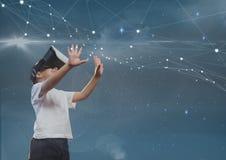 Glücklicher Junge in VR-Kopfhörer, der Sterne gegen blauen Himmel berührt Stockfoto