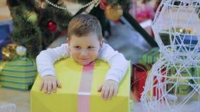 Glücklicher Junge wünschen nicht neues Jahr ` s Geschenke und traurig Kind, das unter Weihnachtsbaum sitzt stock video footage