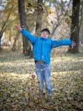 Glücklicher Junge wirft Blätter in Herbst Park stockfoto