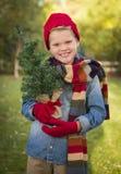 Glücklicher Jungen-tragende Feiertags-Kleidung, die kleinen Weihnachtsbaum hält Stockfotos