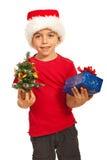 Glücklicher Jungenholding Weihnachtsbaum und -geschenk Stockbilder