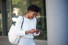 Glücklicher junger afrikanischer Frauenlesetext am Handy Stockfotos