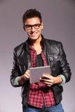 Glücklicher junger beiläufiger Mann mit Tablette Stockfotos