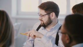 Glücklicher junger Berufsmann-CEO, der Arbeit mit Kollegen hinter Tabelle bei der Teambesprechung im modernen hellen Büro bespric stock footage