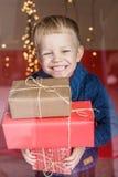 Glücklicher junger blonder Junge mit Geschenkbox Weihnachten Geburtstag stockfotografie