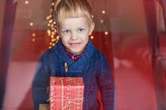 Glücklicher junger blonder Junge mit Geschenkbox Weihnachten Geburtstag Lizenzfreies Stockbild