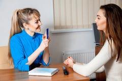 Glücklicher junger erwachsener blonder Doktor berät ihren Patienten Stockfotos