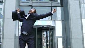 Glücklicher junger Finanzier, der Siegerzeichenbürogebäude, erfolgreiche Investition zeigt stock footage