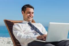 Glücklicher junger Geschäftsmann auf einem Klappstuhl unter Verwendung seines Computers Stockfotografie