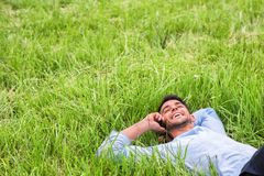 Glücklicher junger Geschäftsmann, der auf dem grünen Gras liegt Unterhaltung am Telefon lizenzfreies stockbild