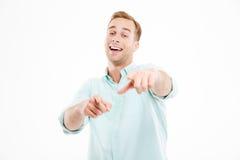 Glücklicher junger Geschäftsmann, der auf Sie lacht und zeigt Stockfotos