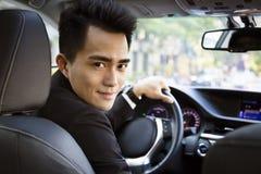 Glücklicher junger Geschäftsmann, der in das Auto fährt stockfoto