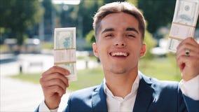 Glücklicher junger Geschäftsmann, der einen großen Geldbetrag in seinen Händen hält Er steht in der Straße nahe der Büromitte ode stock video footage
