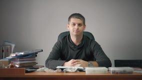 Glücklicher junger Geschäftsmann, der im Büro mit Geschäftspapieren auf Tabelle sitzt Arbeiten des gut aussehenden Mannes, schrei stock footage