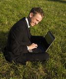 Glücklicher junger Geschäftsmann, der im Park arbeitet Lizenzfreies Stockfoto