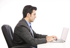 Glücklicher junger Geschäftsmann, der an Laptop arbeitet Stockfoto
