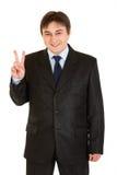 Glücklicher junger Geschäftsmann, der Sieggeste zeigt Stockbilder