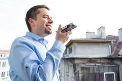 Glücklicher junger Geschäftsmann, der Sprachmitteilung durch seinen Smartphone sendet stockbilder