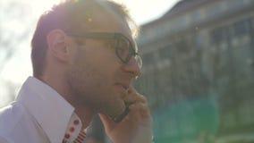 Glücklicher junger Geschäftsmann, der am Telefon in der Stadtstraße spricht stock video footage