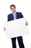 Glücklicher junger Geschäftsmann, der unbelegte weiße Karte anhält lizenzfreies stockbild