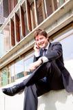 Glücklicher junger Geschäftsmann mit Mobiltelefon stockfoto
