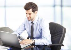 Glücklicher junger Geschäftsmann unter Verwendung des Laptops in seinem Büro lizenzfreie stockfotografie