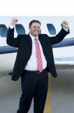 Glücklicher junger Geschäftsmann vor Geschäftsflugzeug Lizenzfreies Stockfoto