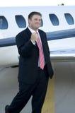 Glücklicher junger Geschäftsmann vor Geschäftsflugzeug Stockbild