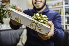 Glücklicher junger gut aussehender Mann, der jemand ein Geschenk hält und gibt stockbilder
