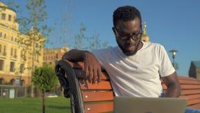 Glücklicher junger Herr, der an neue Strategien beim draußen arbeiten denkt stock video footage